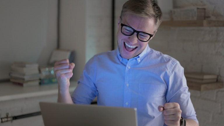 Businessman Celebrating Success at Work at Night